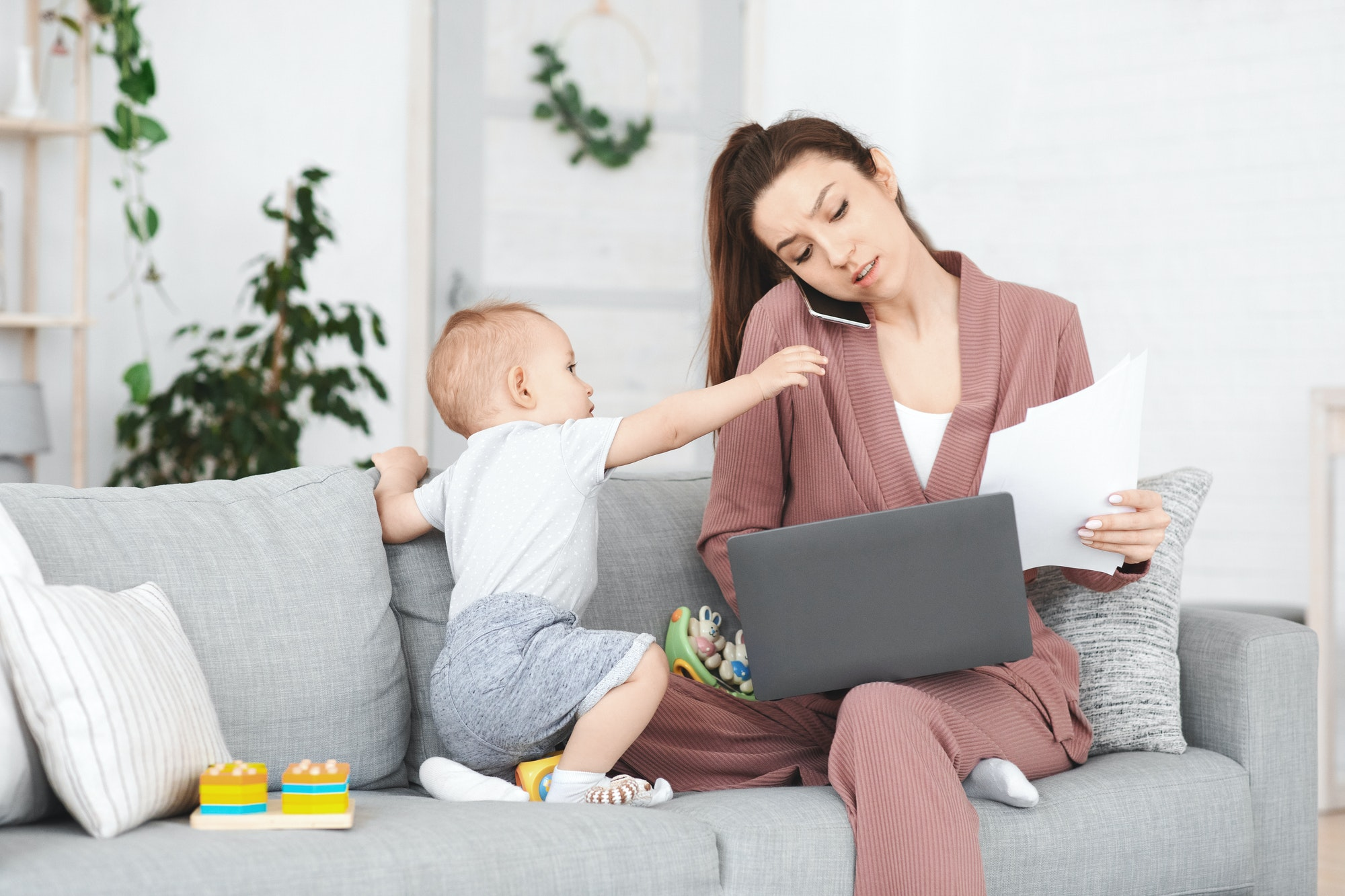 Business And Maternity. Annoyed mom trying to work while toddler distracting her