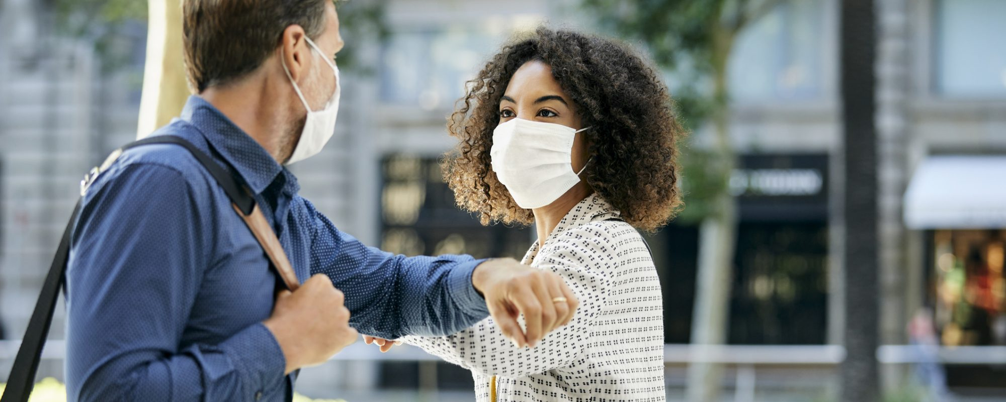 Business people greeting in city. Male and female entrepreneurs talking while avoiding handshake during pandemic. They are maintaining social distance.