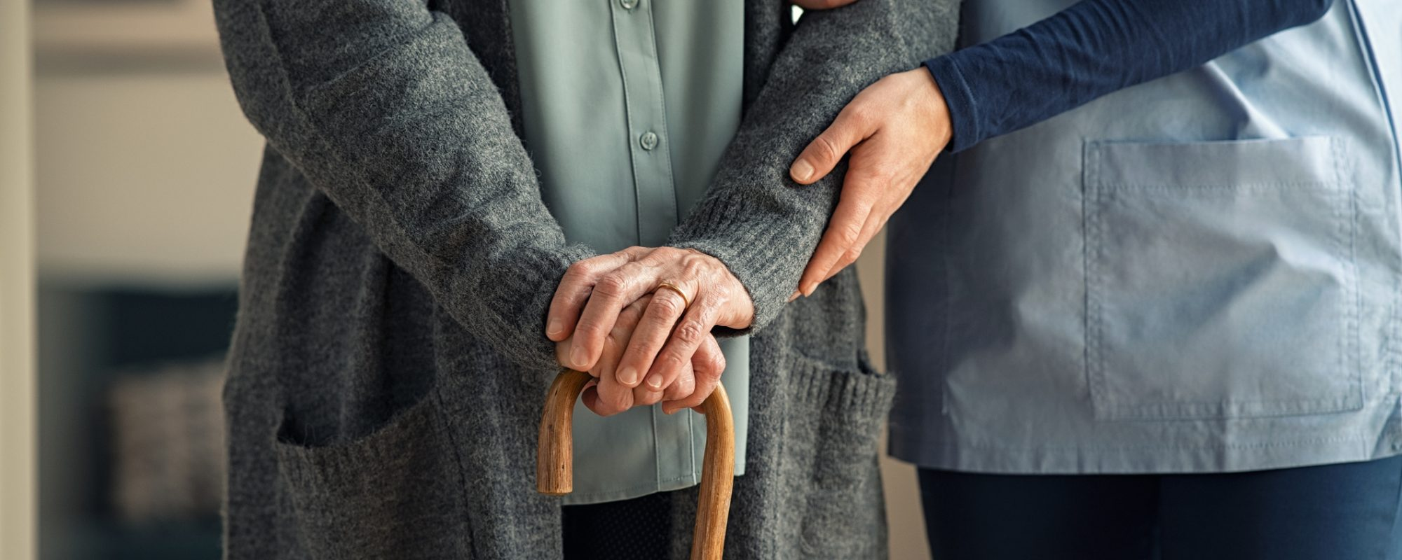 Close up hands of caregiver doctor helping old woman at private clinic. Close up of hands of nurse holding a senior patient with walking stick. Elder woman using walking cane at nursing home with nurse holding hand for support.