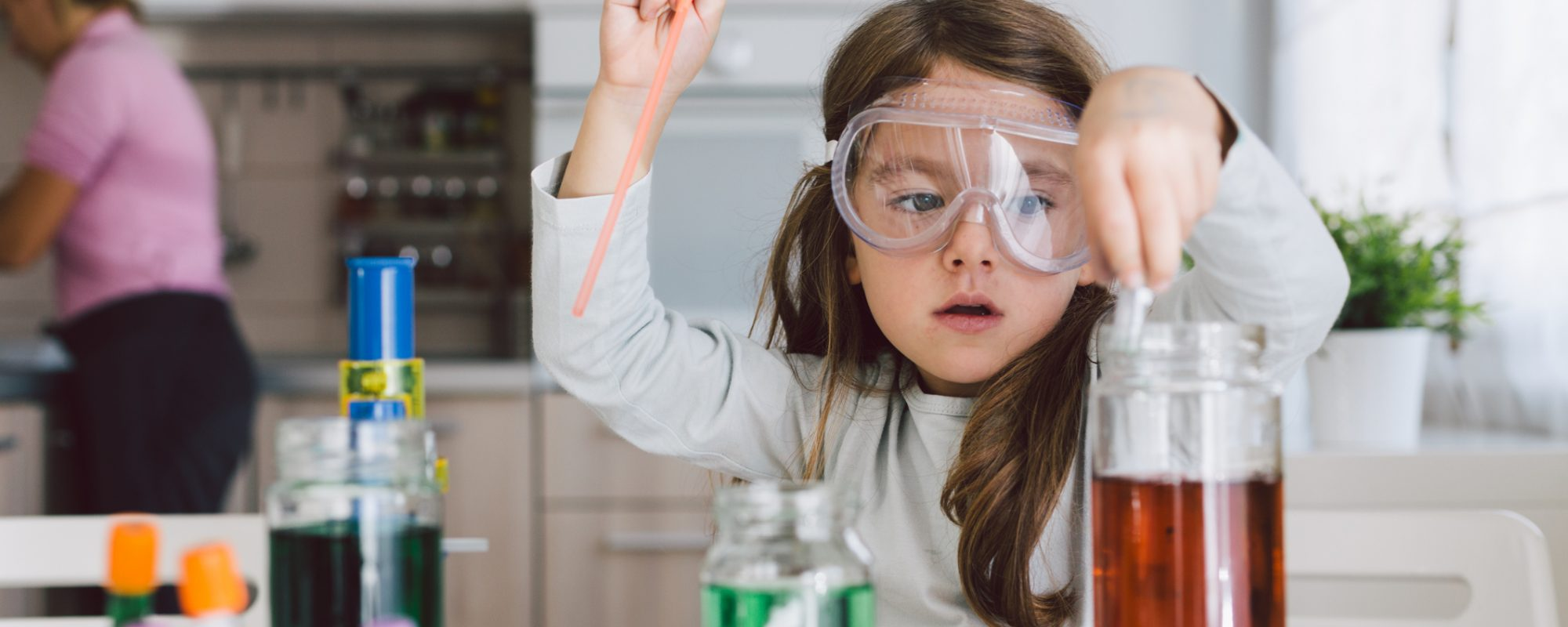 Child playing making some experiments , while her mother working in the kitchen