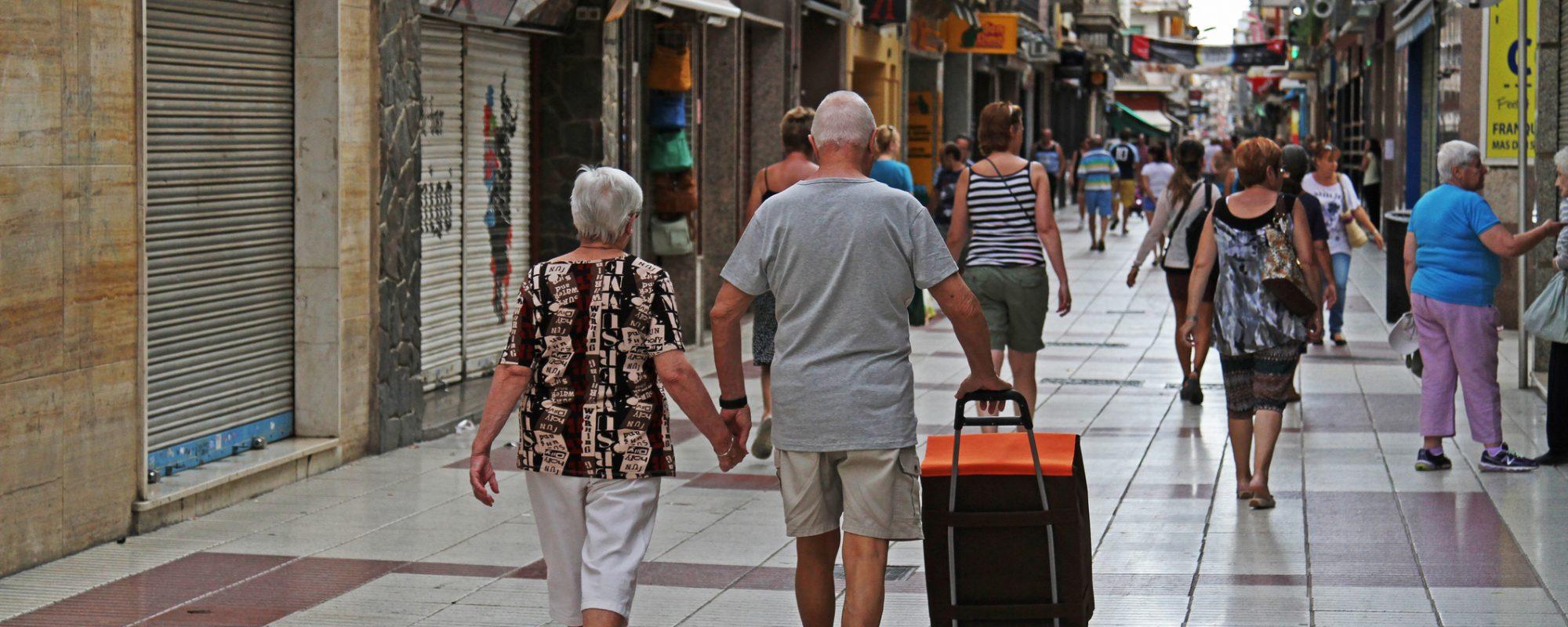 Calella, Spain - September 13, 2014: Rear view of people walking  on a pedestrian street Carrer Esglesia in Calella