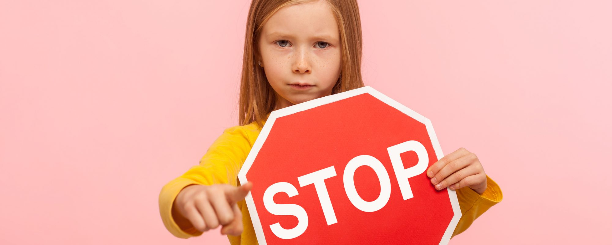 Portrait of cute serious bossy little girl holding Stop symbol, showing red traffic sign and pointing to camera, warning you about road safety rules. indoor studio shot isolated on pink background