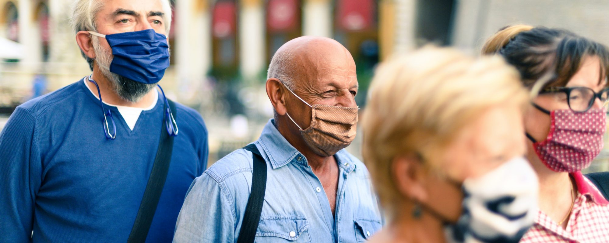 Crowd of adult people walking on city street with face mask on - New normal lifestyle concept - Focus on bald man with brown protective mask